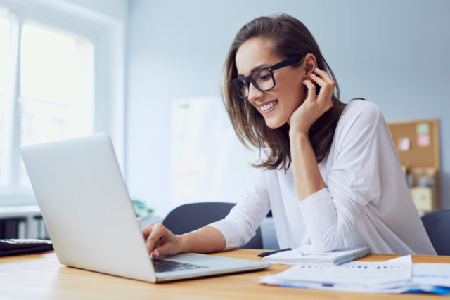Portrait of veautiful cheerful young businesswoman working on laptop and laughing in home office